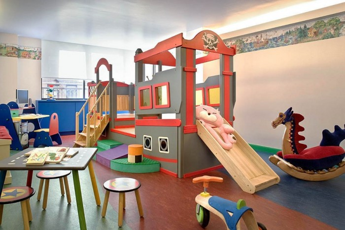 Pirate-fantasy-childs-playroom-with-bordered-walls-and-dragon-rocking-horse-700x467