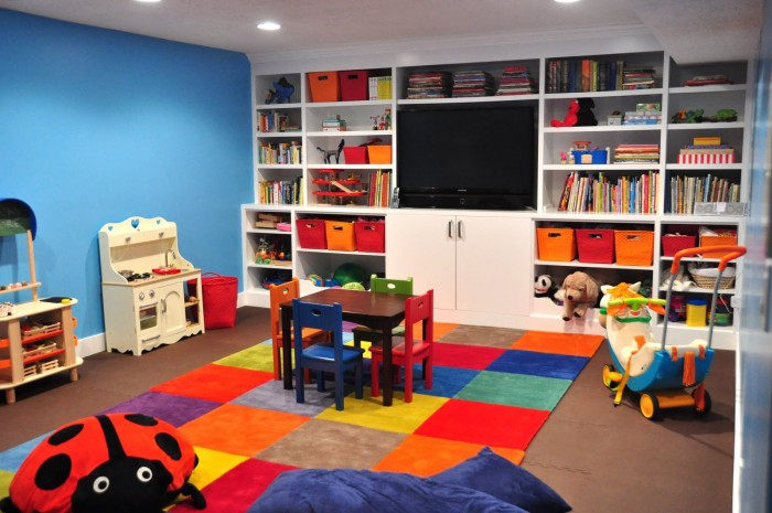 patchwork-rug-of-bright-multicolored-squares-built-in-storage-and-flatscreen-TV-700x465