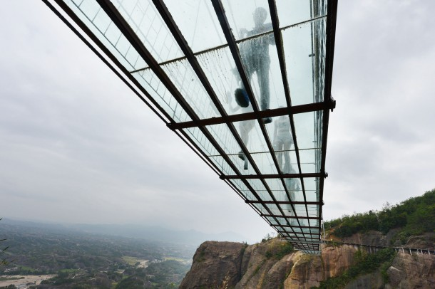 PINGJIANG, CHINA - SEPTEMBER 24: (CHINA OUT) Tourists walk on a suspension bridge made of glass at the Shiniuzhai National Geological Park on September 24, 2015 in Pingjiang County, China. The 300-meter-long glass suspension bridge, with a maximum height of 180 meters, opened to the public on Thursday. (Photo by ChinaFotoPress/ChinaFotoPress via Getty Images)